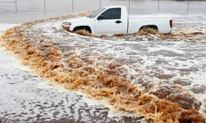 A truck creates a wake as its driver tries to navigate a severely flooded street in Phoenix.