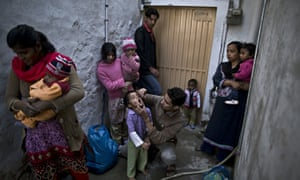 A health worker marks an infant after immunisation with anti-polio drops in Lahore, Pakistan