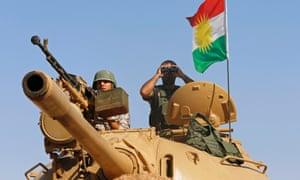 Kurdish peshmerga fighters man a tank against Islamic State militants