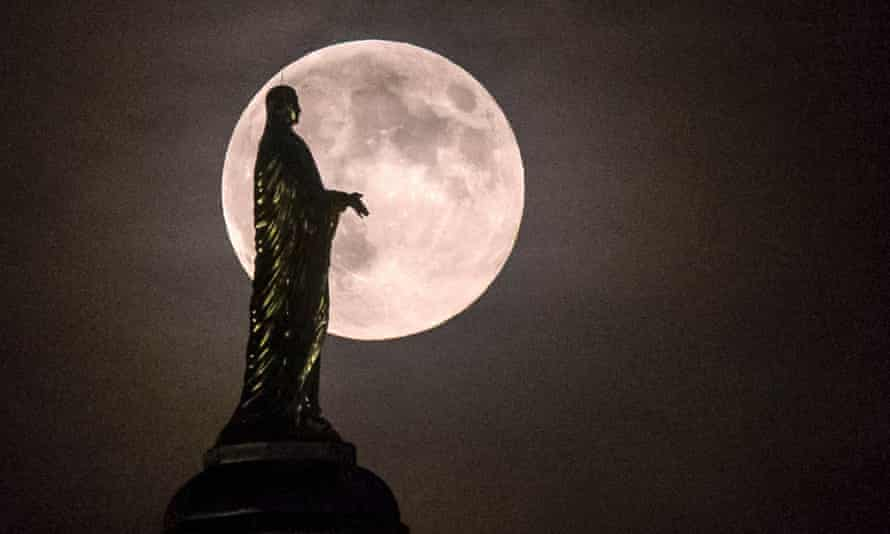 The full moon silhouettes the statue of the Virgin Mary on top the University of Notre Dame's golden dome in South Bend, Indiana, US.