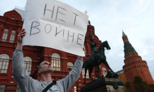 """A man holds a sign during a protest against the conflict in eastern Ukraine in the centre of Moscow on 28 August. The sign reads: """"No war"""""""