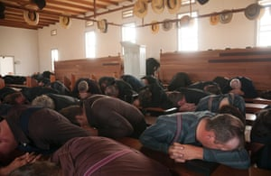 Mennonite men praying during the most dramatic moment in mass at the Manitoba colony