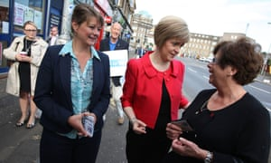 Scotland's Deputy first minister, Nicola Sturgeon, and Plaid Cymru Leanne Wood (foreground, left), stop to talk to a woman whilst on a walk-about in Glasgow yesterday.
