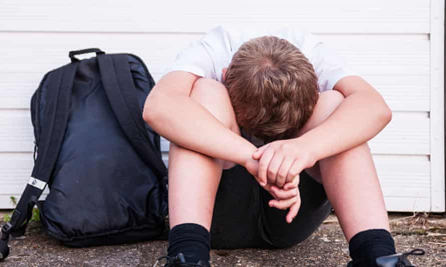 A boy of 10 looking sad and depressed in his school uniform.