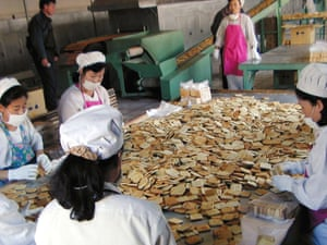 North Korean workers pack vitamin-and mineral-enriched biscuits at a factory in Sinuiju city, North Korea.