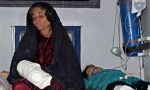 An injured woman and child wait to be admitted to hospital after rocket strike on Afghan wedding