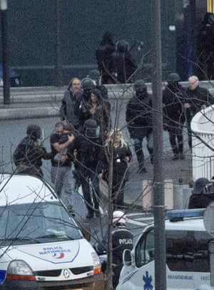 A man holding a child is among hostages rushed away by police from the kosher grocery store.