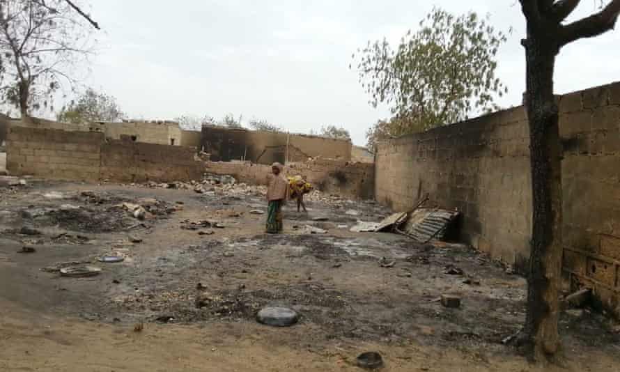 A young girl stands amid the burned ruins of Baga in 2013