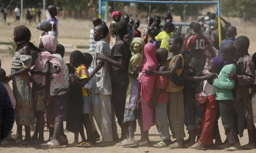 Children left homeless after attacks by Boko Haram line up in a displaced people camp in Yola, Nigeria