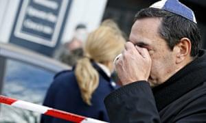 A man  wearing kippa cries near a kosher