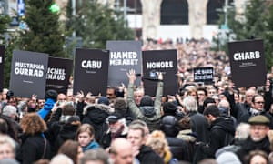 Silent marchers hold aloft the names of those killed at Charlie Hebdo at a demonstration in Lille