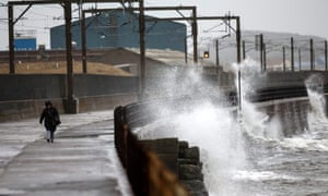 A wave crashes against the sea wall on the Ayrshire coast in Scotland on Friday.