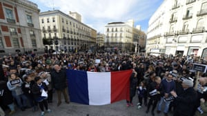 """Madrid, Spain People hold placards reading in French """"I am Charlie"""" behind a french flag during a public show of solidarity on Plaza del Sol."""