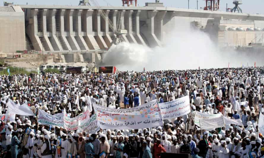 Hundreds of Sudanese holding banners supporting their President Omar Al-Bashir during the inauguration of the massive hydro-electric dam in Merowe, north of Khartoum, on 3 March 2009.