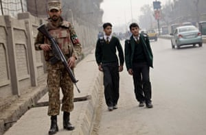 Pakistani schoolchildren leave the Army Public School as a soldier stands guard