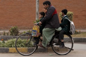 Children get a ride home from the Army Public School by bike after it was reopened