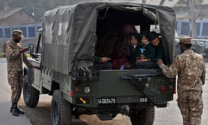 Pakistani soldiers escort students as they leave the Army Public Schoo