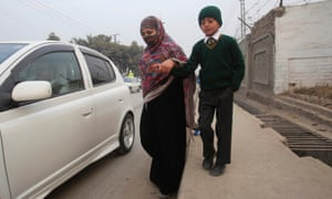 A boy walks with his mother on the way to the school