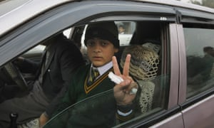 Mohammad Baqair, who survived last month's Taliban attack, flashes a victory sign on his way to the Army Public School this morning