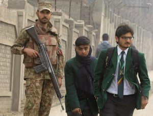 Pakistani students walk into school as a soldier stands guards