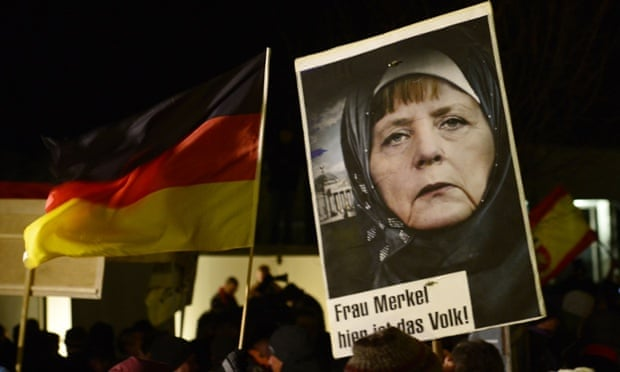 An image of Angela Merkel manipulated to make it look like she's wearing a hijab, at a Pegida rally in Dresden.