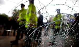 police officers in fluorescent jackets seen through cracked glass