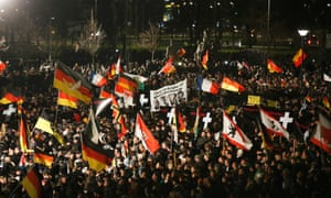 Supporters of anti-immigration movement Pegida hold flags during a demonstration in Dresden