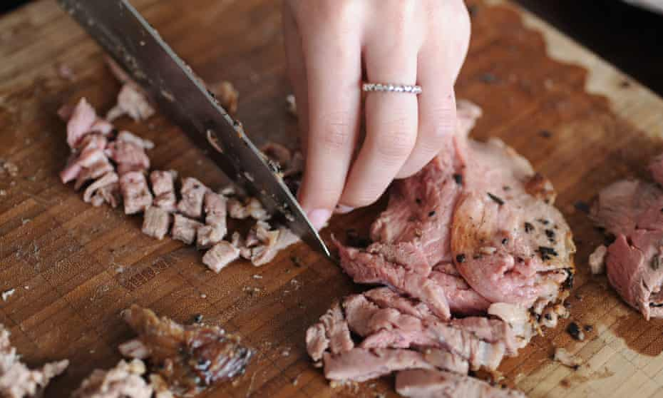a lady chopping up leftover lamb