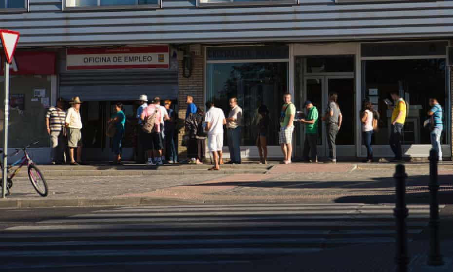 Jobseekers wait in a queue outside an employment centre in Madrid, Spain.