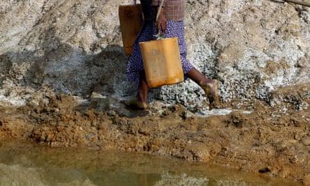 woman walks barefoot by mine water