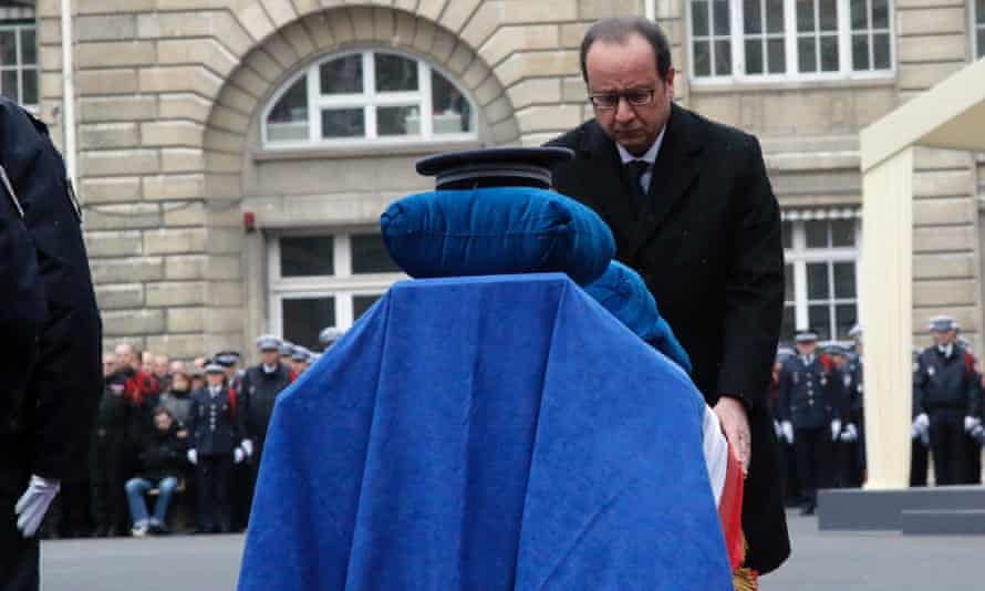 The French president, François Hollande, stands in front of the coffin of police officer Ahmed Merabet during a national tribute for all the police officers killed last week.