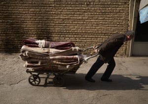 A worker pulls a cart stacked with handwoven Persian carpets at Tehran's carpet bazaar.
