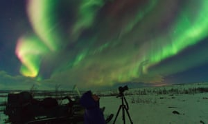 A photographer at the Aurora Safari Park looks up at a stunning showing of the northern lights.