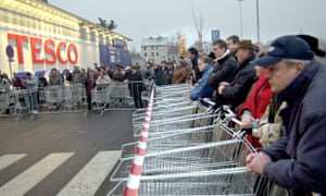 Customers with shopping carriages stand ready