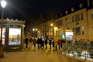 Customers wait in line at Pigalle newsstand in Paris