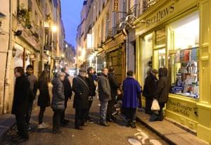 A queues of people line up in the Saint Germain-des-Pres area of Paris