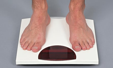 Legs of a man standing on weighing scales