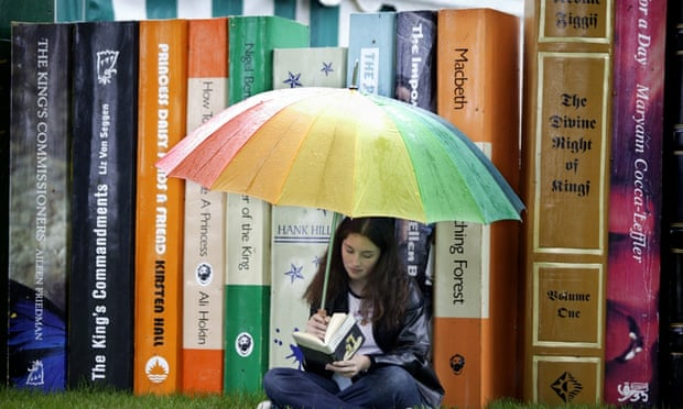Teenager reading at Hay on Wye under an umbrella