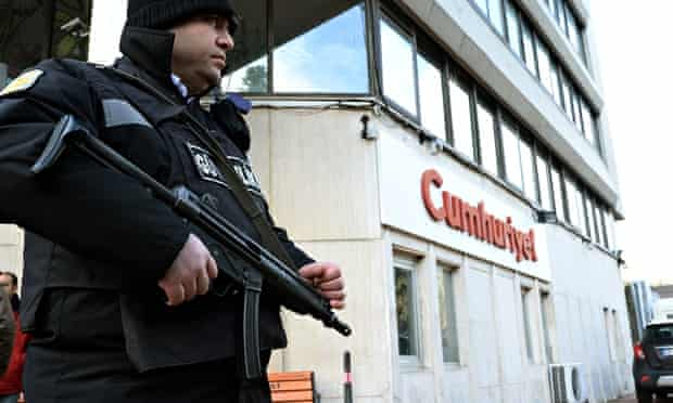 A police officer stands guard at the entrance of Cumhuriyet, the leading Turkish secular newspaper