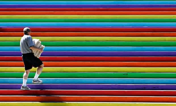 Man walks up rainbow stairs