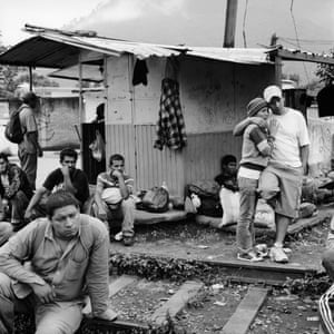 Central American migrants wait for a train by the track. There is no migrant shelter in Orizaba and migrants wait out in the open, often for days, to catch moving freight trains