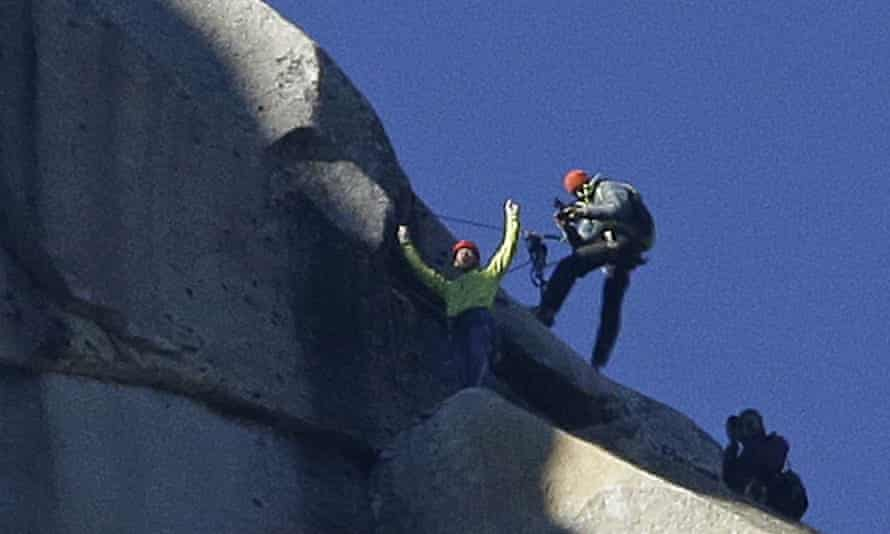 Tommy Caldwell, top, raises his arms after reaching the summit of El Capitan.