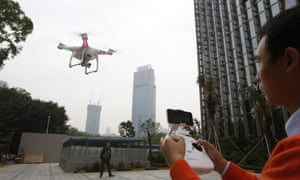 A staff member from DJI Technology Co. demonstrates the remote flying with his Phantom 2 Vision+ drone in Shenzhen, south China's Guangdong province
