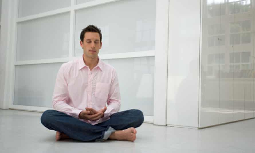 A man meditating in an office.