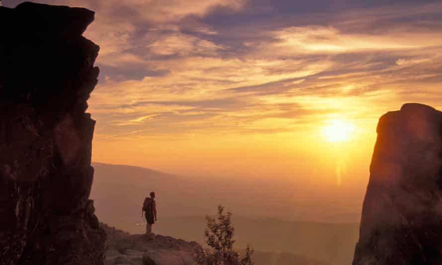 A hiker at sunset on Humpback Rocks on the Appalachian Trail, in Virginia, US.