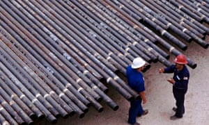 two workers in hard hats stand next to oil drilling pipes