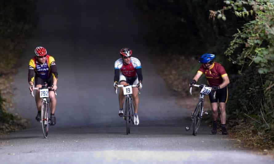 A cyclist pushes his bike up a hill as two others ride past
