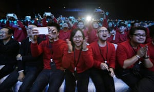 Xiaomi staff and users of Xiaomi phones react at the launch ceremony of the Mi Note in Beijing January 15, 2015.