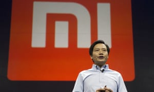 Xiaomi chairman Lei Jun in front of the company's logo.
