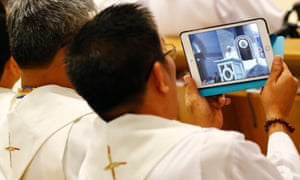 A priest takes a photo on his tablet as Pope Francis leads the mass at the Manila Cathedral.